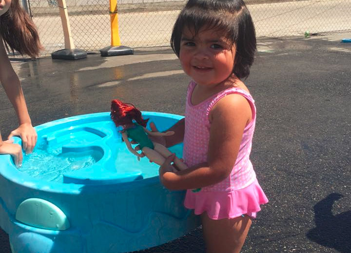 Young little girl on a pink bathing suit while holding a barbie beside a plastic pool at A Preschool & daycare Serving Armona, CA