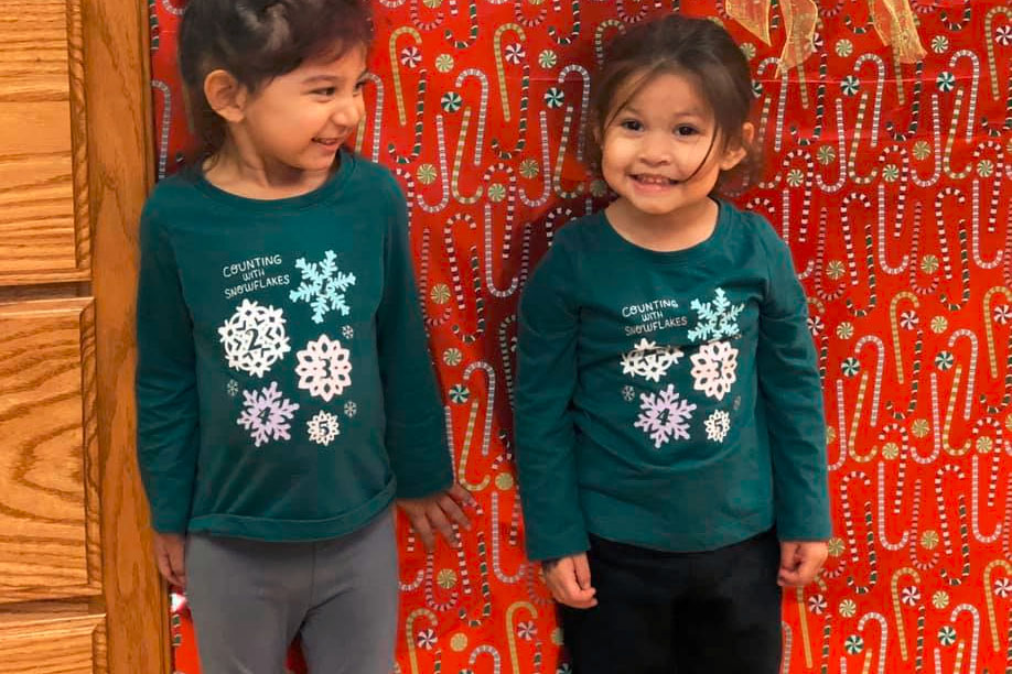 Two little preschool girls sisters wearing Christmas sweat shirt smiling happy little preschool girl playing with educational building blocks at A Preschool & daycare Serving Armona, CA