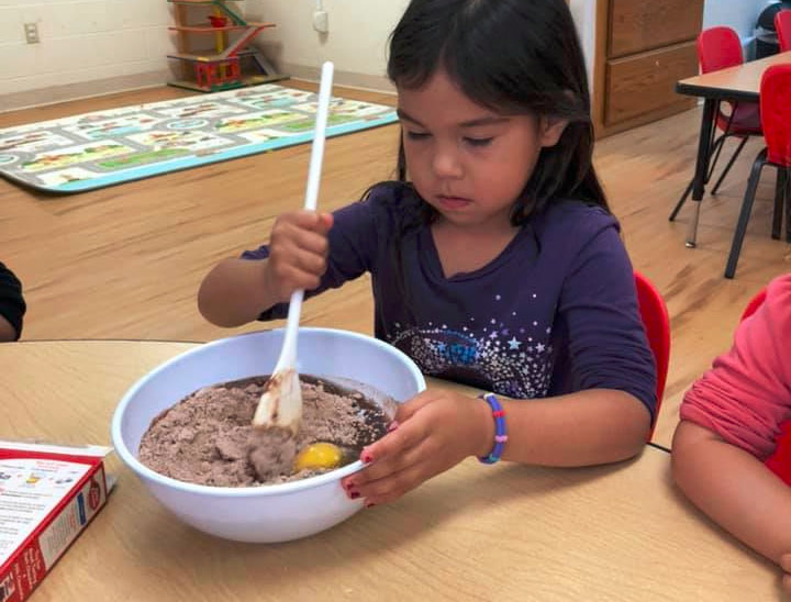 Young preschool girl mixing a bowl of flour, egg and chocolate at A Preschool & daycare Serving Armona, CA
