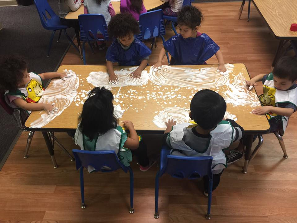 Group of toddlers playing white powder on the table at A Preschool & daycare Serving Armona, CA
