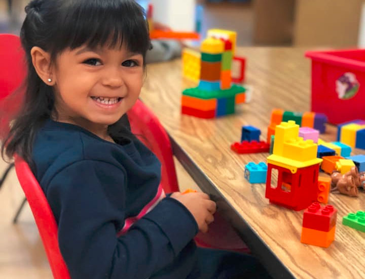 happy little preschool girl playing with educational building blocks at A Preschool & daycare Serving Armona, CA