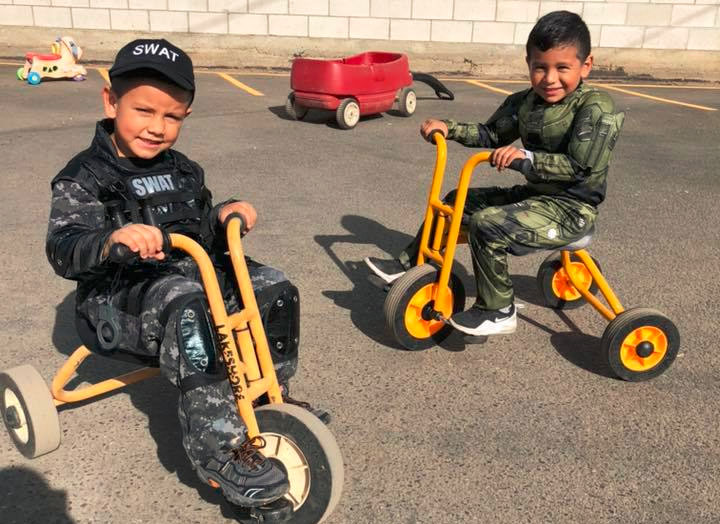 Two little young boys wearing swat attire while riding a 3 wheel bike at A Preschool & daycare Serving Armona, CA