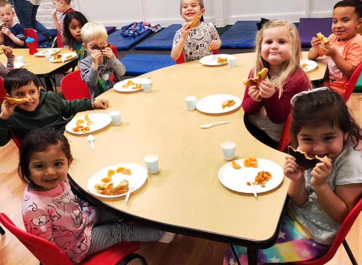 Group of preschoolers eating healthy food at A Preschool & daycare Serving Armona, CA