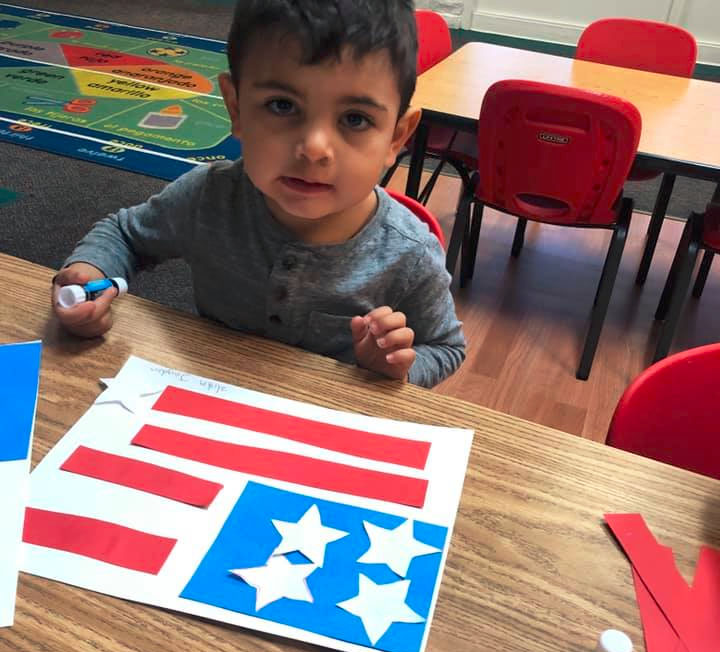 toddler boy sticking together colored cutout papers making the American Flag at A Preschool & daycare Serving Armona, CA