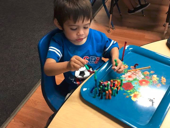 Yong little kid boy playing with educational building blocks at a Preschool & Daycare/Childcare Center serving Miami, FL.
