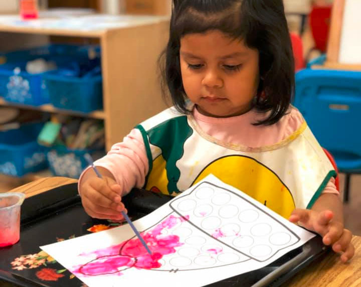 Little young girl showing painting talent on a piece of paper at a Preschool & Daycare/Childcare Center serving Miami, FL.
