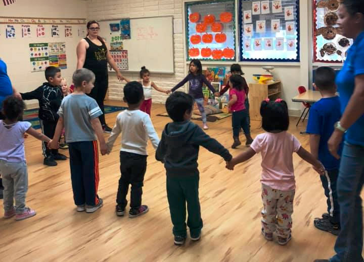Teachers and preschoolers holding each others hands while in circles for their enrichment activity at A Preschool & daycare Serving Armona, CA