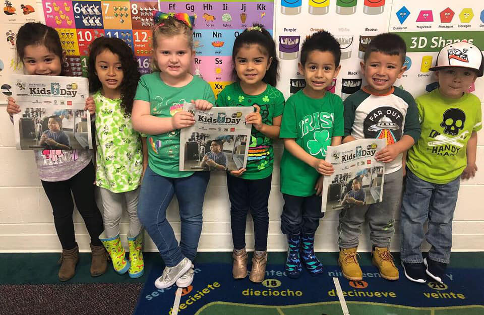 Group of preschool kids standing at the wall holding a school newspaper at A Preschool & daycare Serving Armona, CA