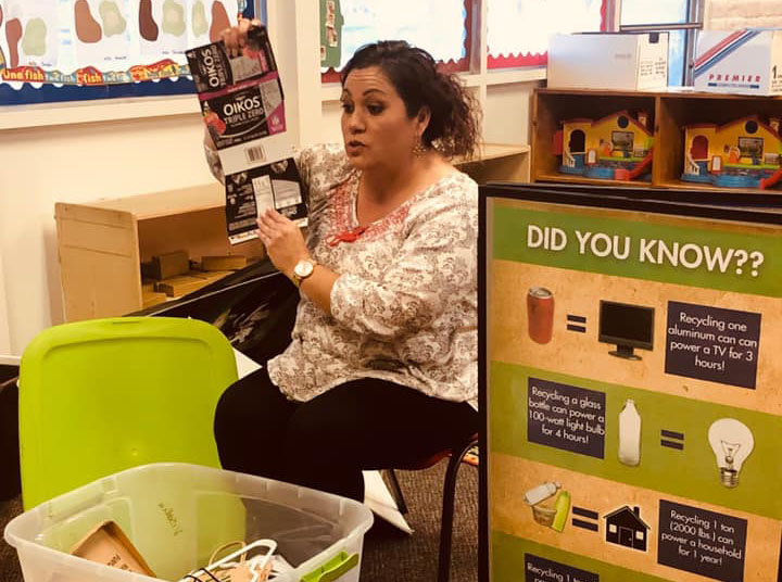 Teacher showing children ways to recycle at A Preschool & daycare Serving Armona, CA
