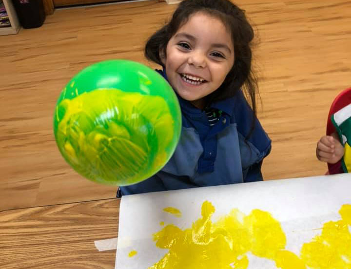 Smiling face young little preschool girl showing a green balloon that was dip into a yellow paint at A Preschool & daycare Serving Armona, CA