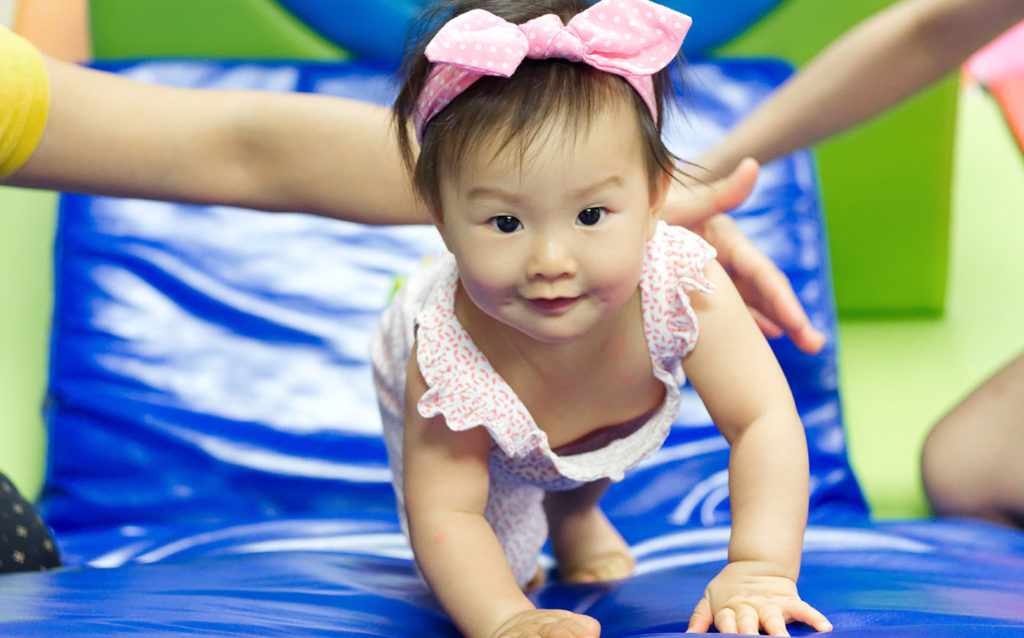 Young little cute Asian baby playing in kid's gym with her mother and teacher. She is crawling to the top of slider with support from her teacher. Child education and development concept at A Preschool & daycare Serving Armona, CA