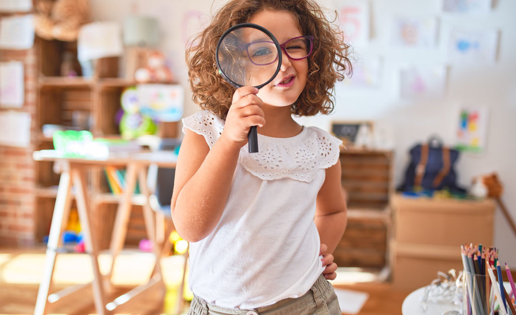Beautiful preschool girl standing wearing glasses using magnifying glass at A Preschool & daycare Serving Armona, CA