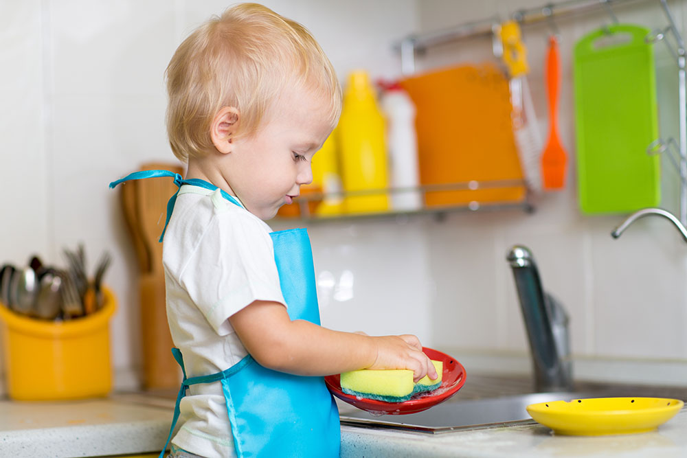 Cute child boy 2 years old washing dishes in kitchen at A Preschool & daycare Serving Armona, CA