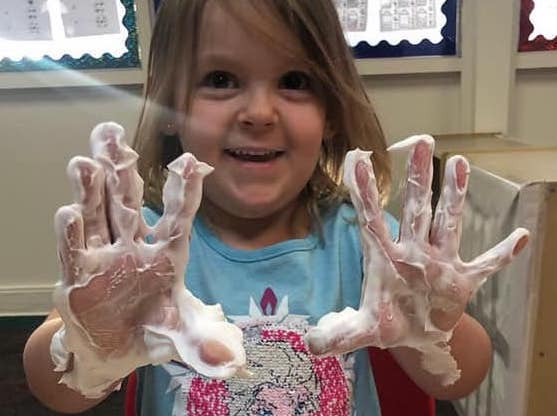 Happy young little girl showing her hands with soap at A Preschool & daycare Serving Armona, CA