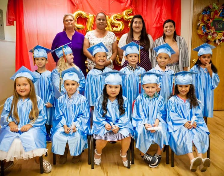Group of graduating preschoolers and their parents at A Preschool & daycare Serving Armona, CA