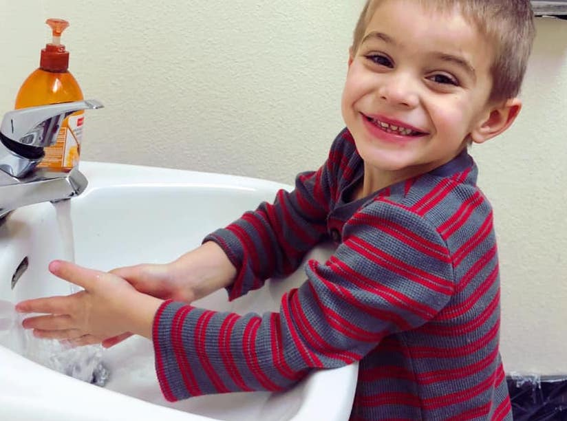 Smiling little young boy washing his hands at the faucet at A Preschool & daycare Serving Armona, CA